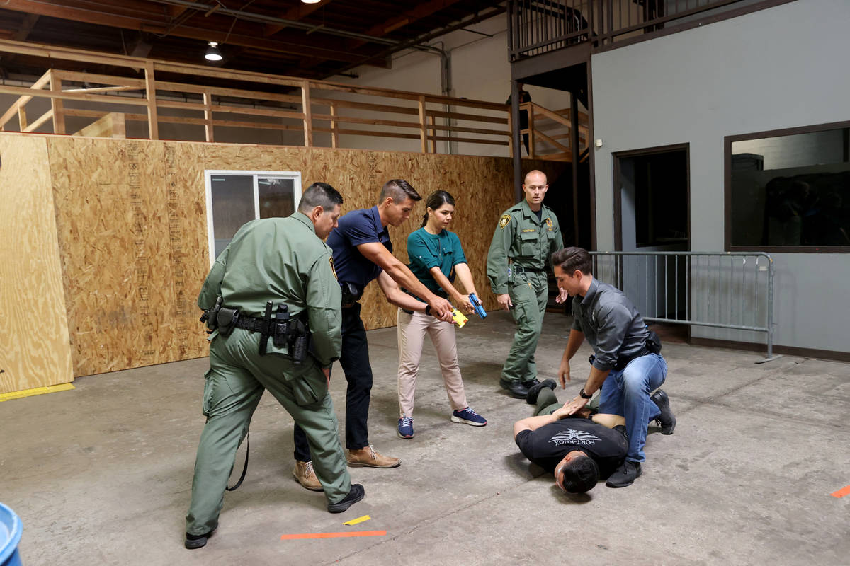 Las Vegas police training officers, J. Esparza, left, and B. Fortner, work with Las Vegas repor ...