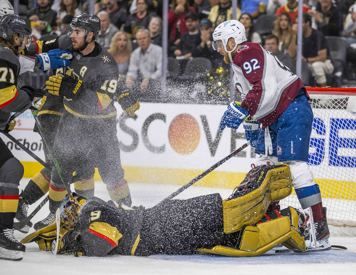 Golden Knights goaltender Marc-Andre Fleury (29)dives on the puck while defended by teammates o ...