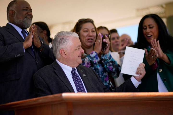 Nevada Democratic Gov. Steve Sisolak holds up a bill newly signed into law Friday, June 11, 202 ...