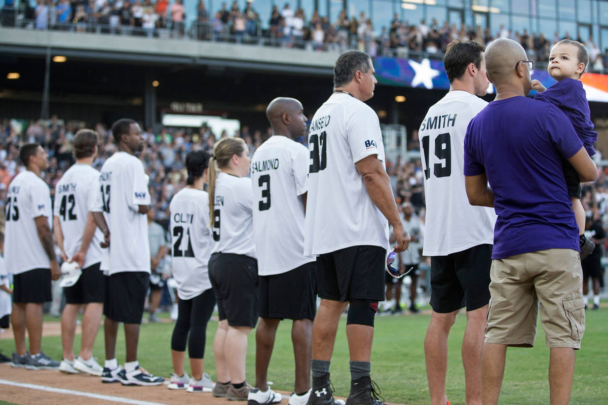 Jordan Rey, 2, right, looks up at the crowd during the playing of the national anthem before th ...