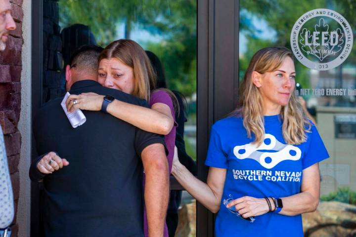Angela Ahmet, center, hugs Rob Hutchinson, President of the Southern Nevada Bicycle Coalition, ...