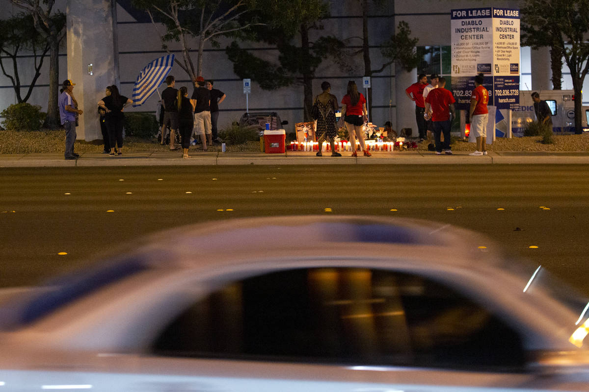 A car drives past a vigil for Walter Anderson near the intersection where he was killed, South ...