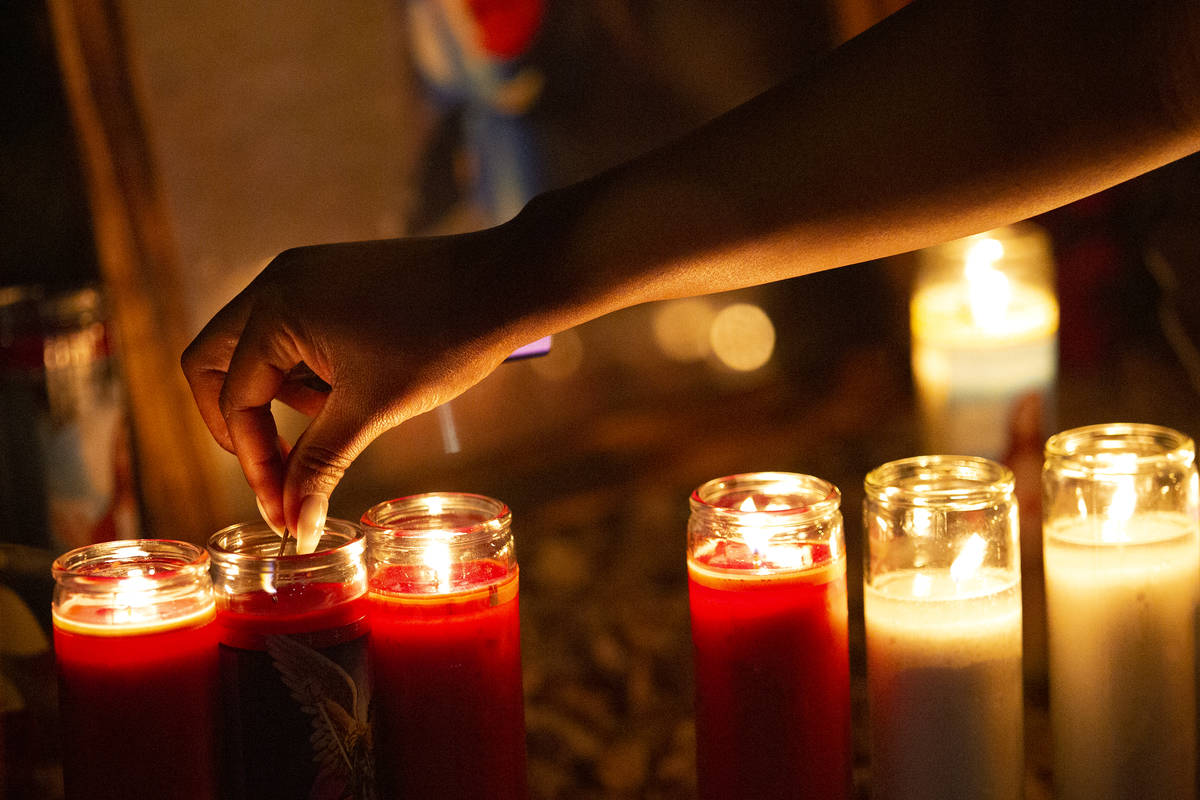 Attendees keep the candles lit at a vigil for Walter Anderson near the intersection where he wa ...