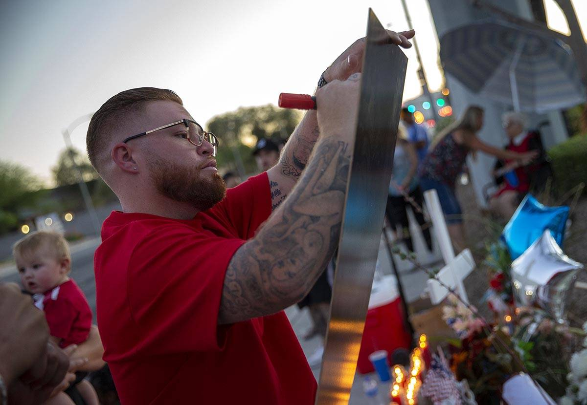 Ryan Anderson writes a message at a vigil for his father, Walter Anderson, near the intersectio ...