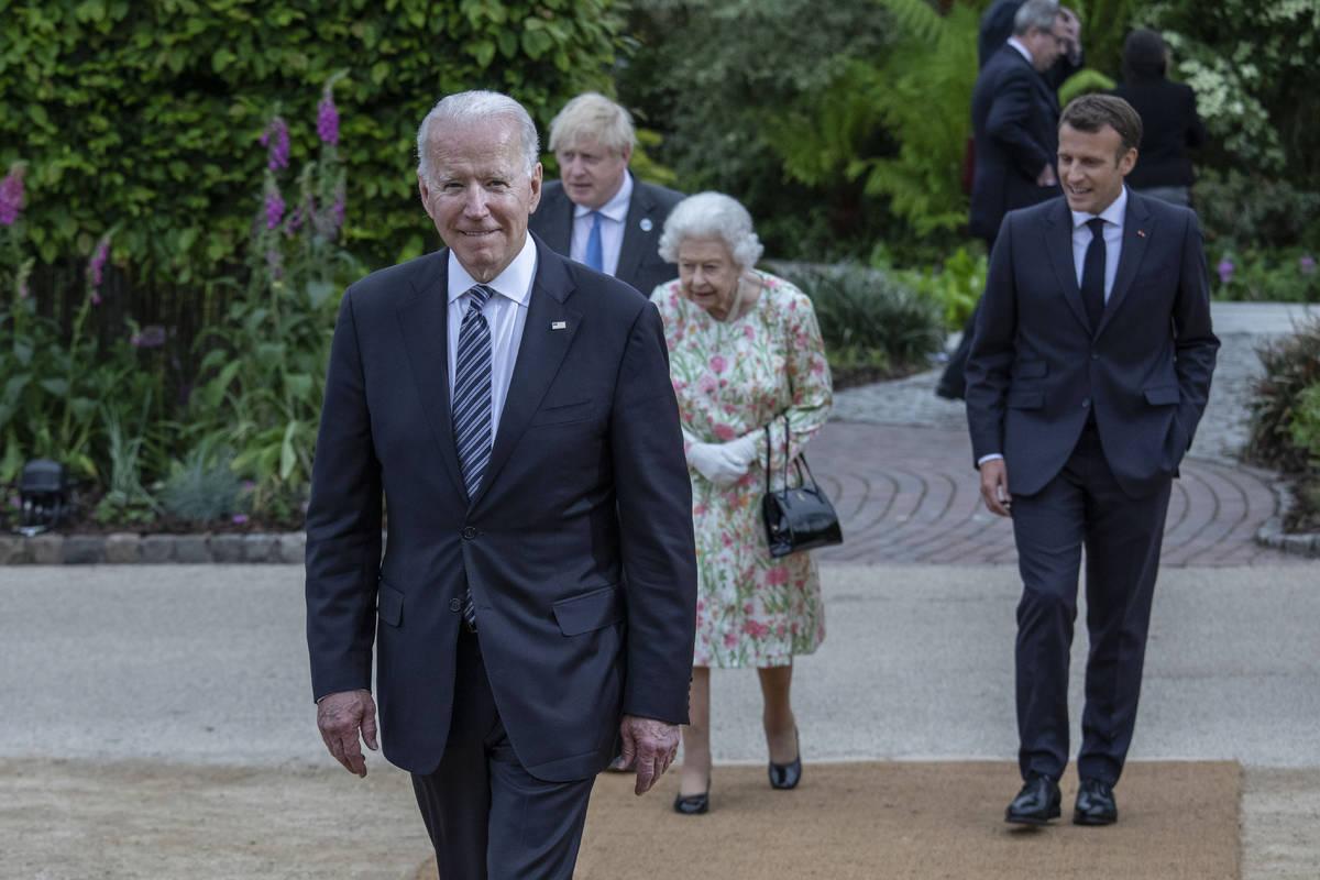 Britain's Queen Elizabeth II, centre walks with French President Emmanuel Macron, Britain's Pr ...
