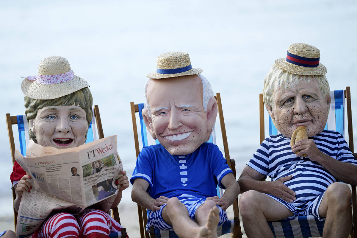 Climate activists from Oxfam, wearing giant heads depicting the leaders of the G7, sit on beach ...