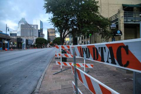 Road block barriers sit on the sidewalk on 6th Street after an early morning shooting on Saturd ...