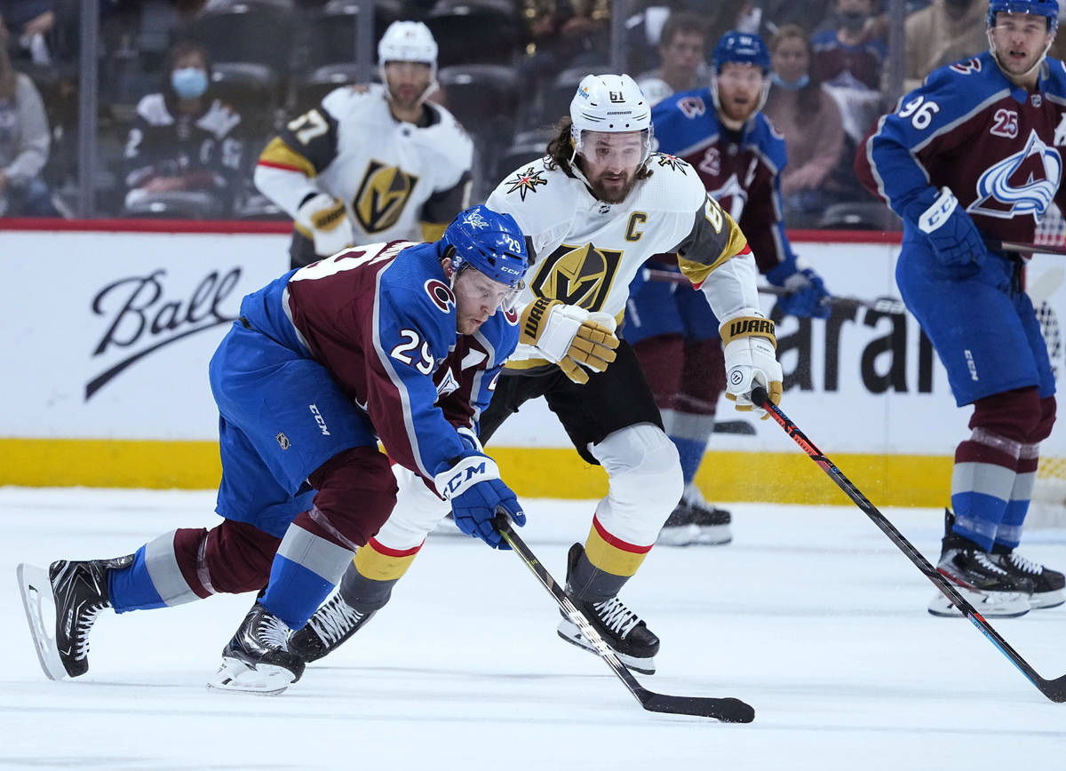 Colorado Avalanche center Nathan MacKinnon (29) moves the puck against Vegas Golden Knights rig ...