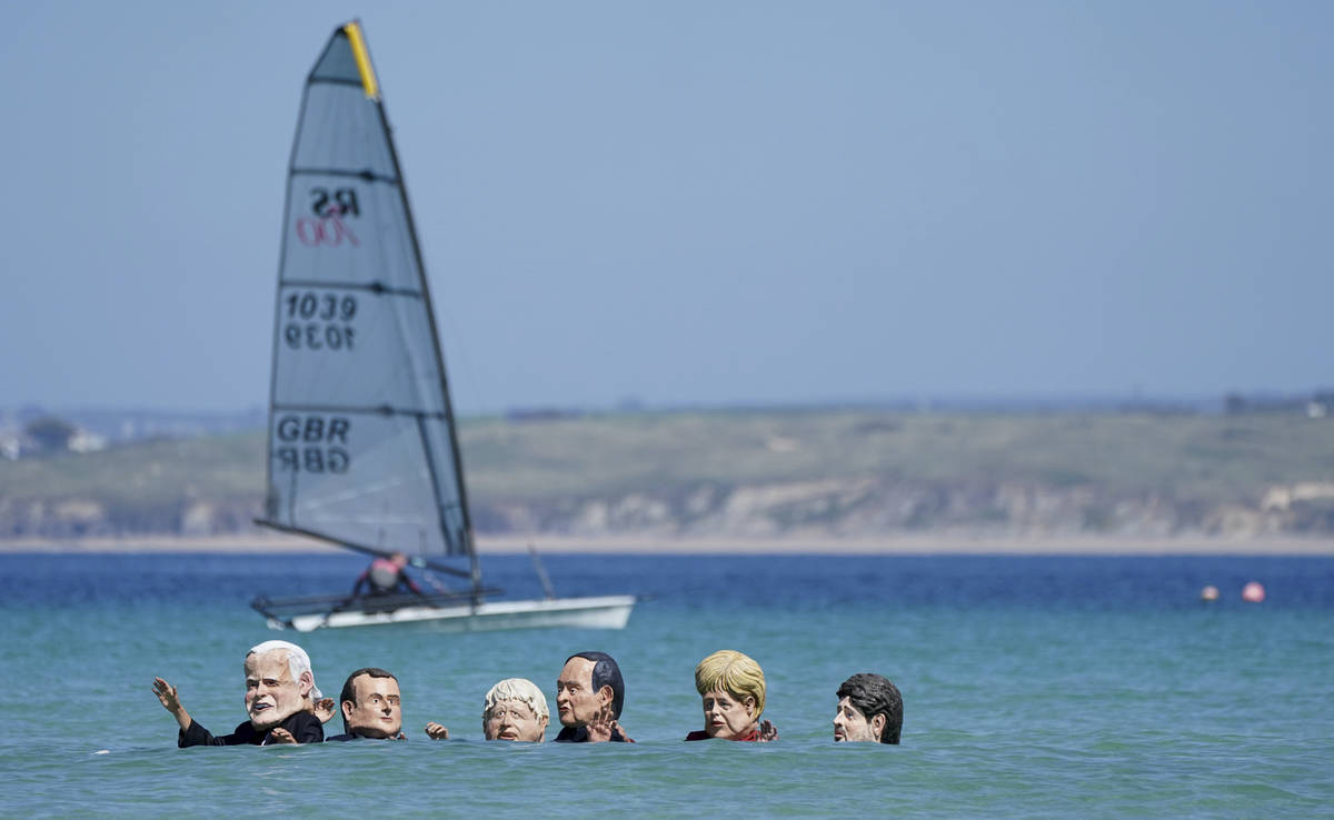 Protestors wearing giant heads portraying G7 leaders swim in the water during a demonstration o ...