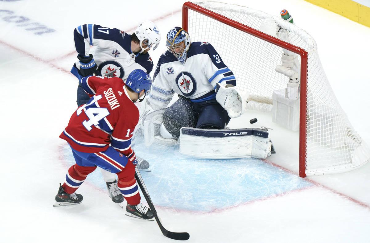 Montreal Canadiens' Nick Suzuki scores a power play goal past Winnipeg Jets goaltender Connor H ...