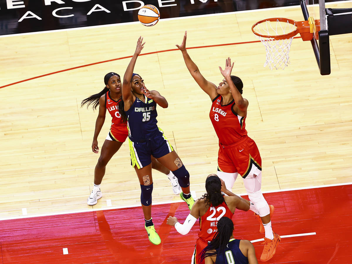 Dallas Wings' Charli Collier (35) shoots under pressure from Las Vegas Aces' Liz Cambage (8) as ...