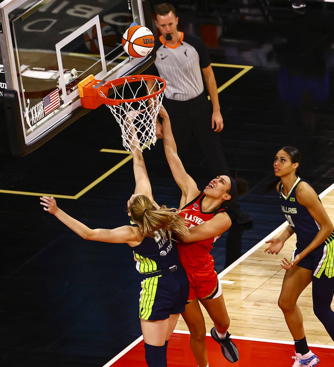Las Vegas Aces' Dearica Hamby (5) goes to the basket against Dallas Wings' Bella Alarie (32) du ...