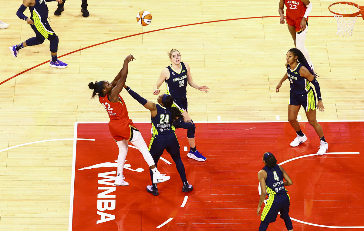 Las Vegas Aces' Chelsea Gray (12) shoots over Dallas Wings' Arike Ogunbowale (24) during the th ...