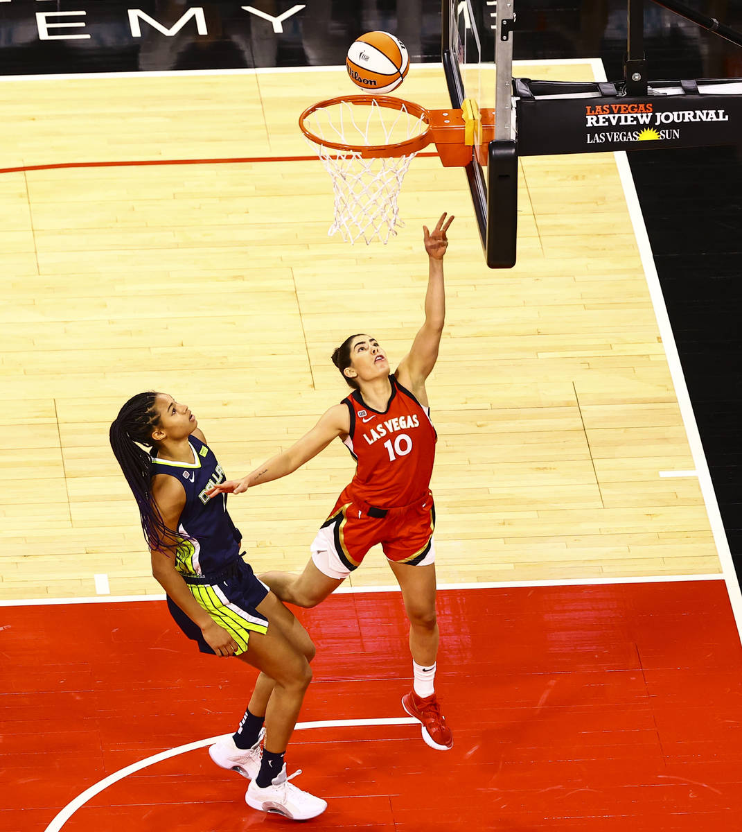 Las Vegas Aces' Kelsey Plum (10) goes to the basket in front of Dallas Wings' Satou Sabally (0) ...