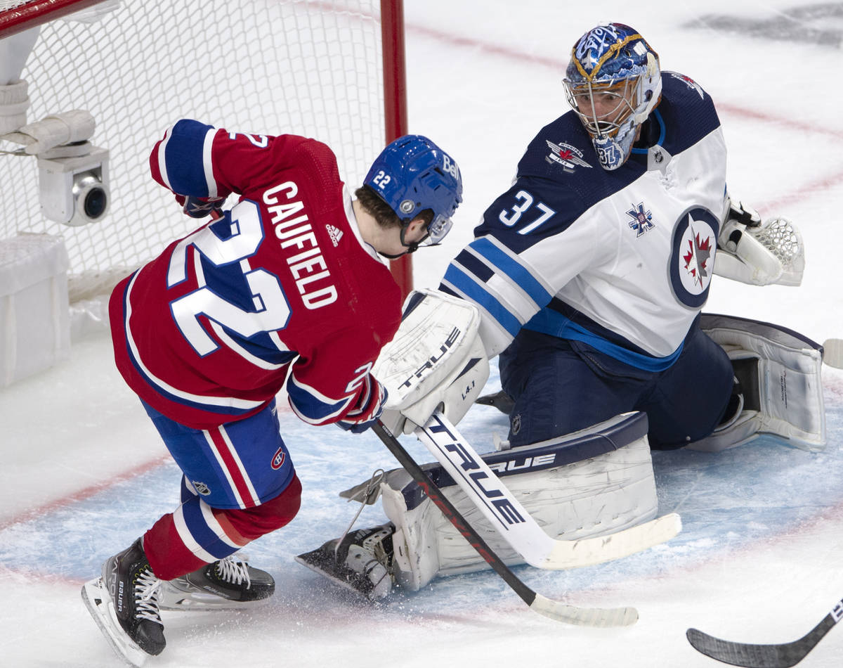 Winnipeg Jets goaltender Connor Hellebuyck (37) stops Montreal Canadiens right wing Cole Caufie ...