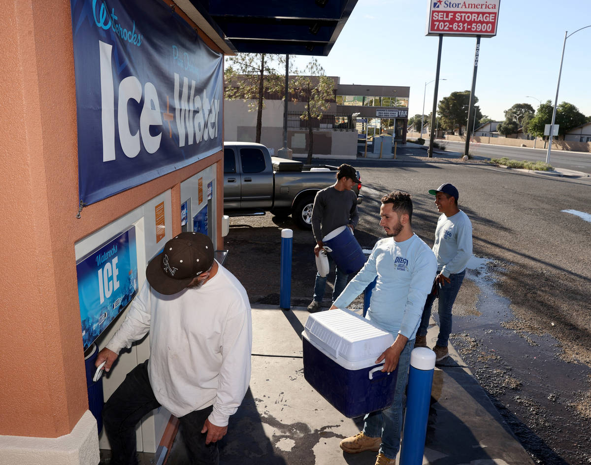 Josue Enrique, from right, Geovanni Lara and Marlon Bonilla wait in line to get ice for their w ...