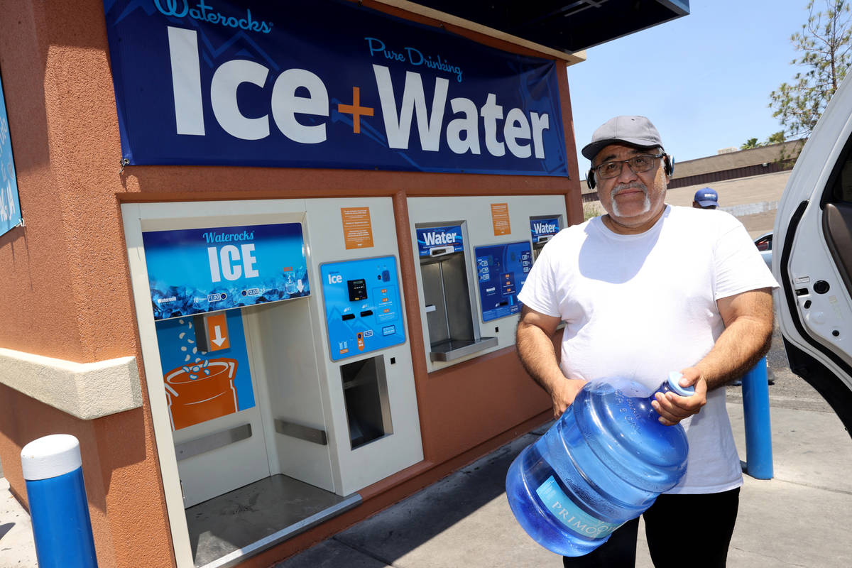 Pedro Soto gets water at a kiosk on the corner of Smoke Ranch Road and Jones Boulevard Monday, ...