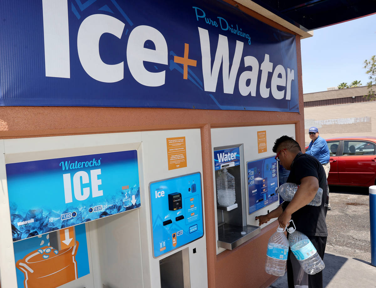 Jamie Juarez, 39, gets water at a kiosk on the corner of Smoke Ranch Road and Jones Boulevard M ...