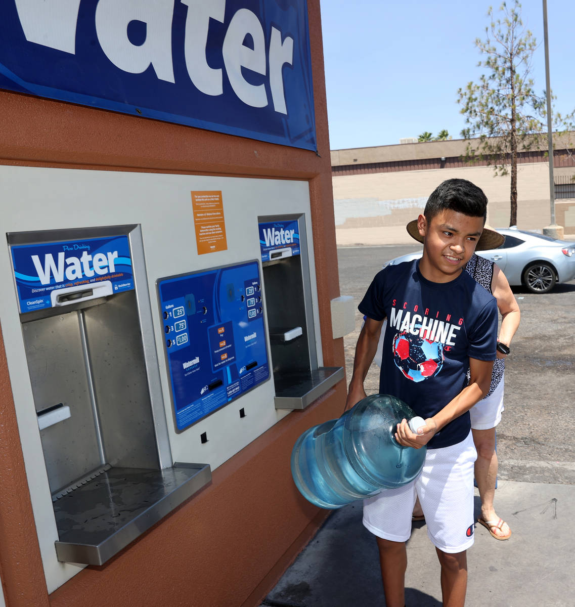 Miguel Lazcano, 14, gets water at a kiosk on the corner of Smoke Ranch Road and Jones Boulevard ...