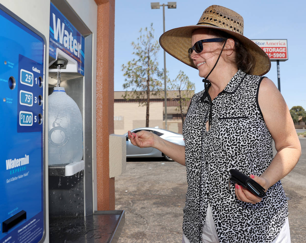 Laurie Baron, 64, gets water at a kiosk on the corner of Smoke Ranch Road and Jones Boulevard M ...