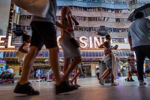 Visitors wander along the shops and casinos at the Fremont Street Experience on Monday, June 14 ...