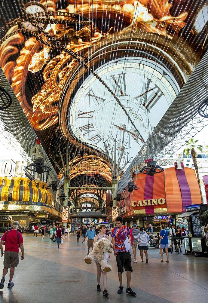 Visitors wander along the shops and casinos as the Viva Vision plays above at the Fremont Stree ...
