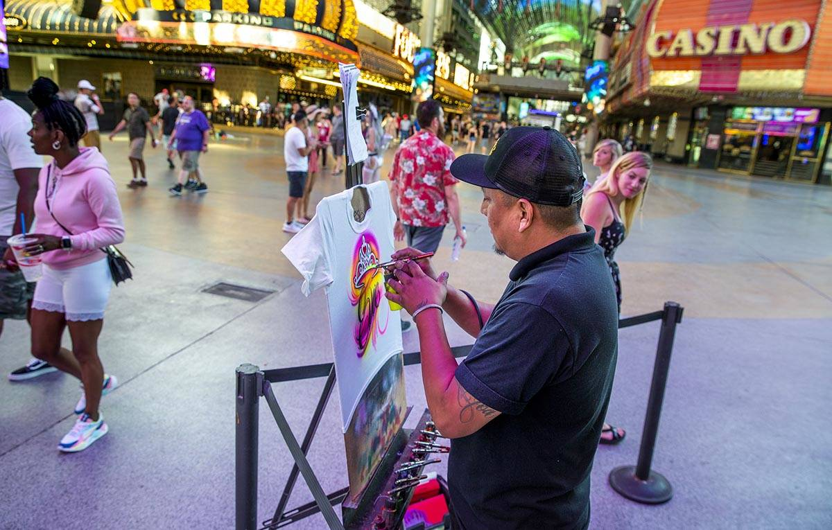 Artist Nate Tsosie with Airbrush Las Vegas creates another custom t-shirt at the Fremont Street ...