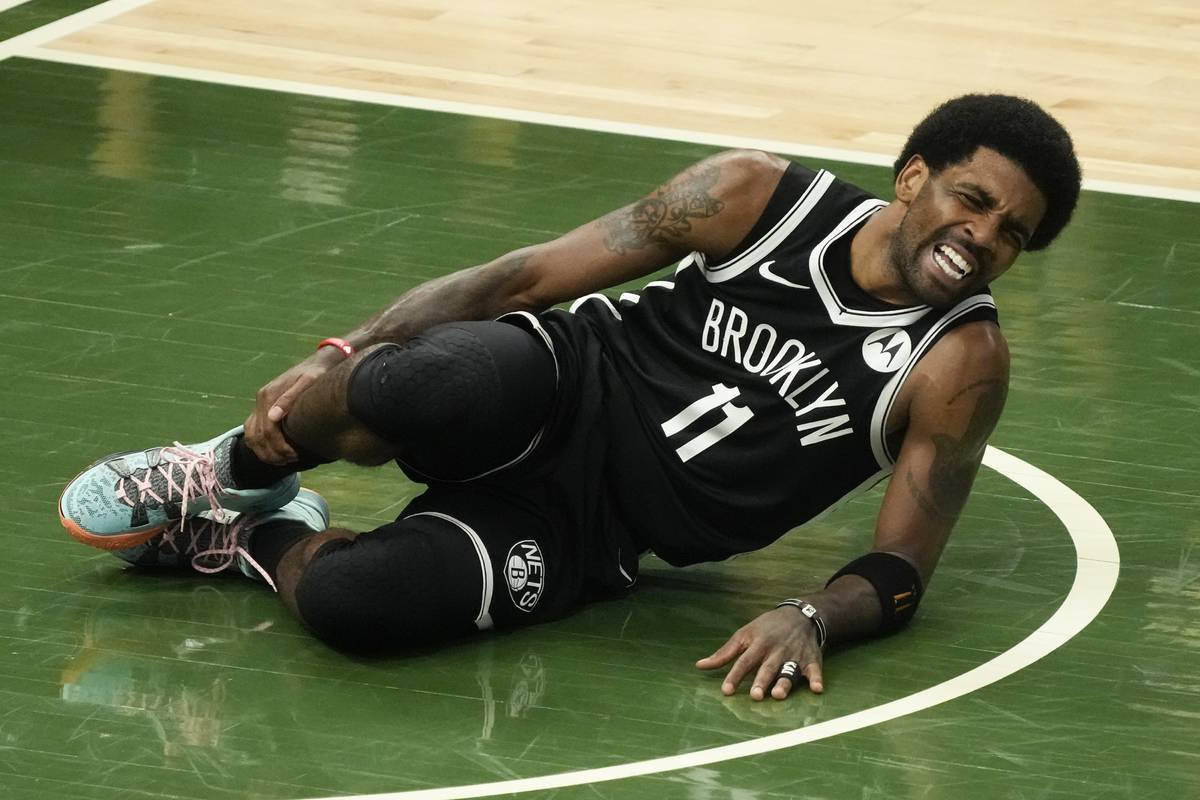 Brooklyn Nets' Kyrie Irving holds his leg after being injured during the first half of Game 4 o ...