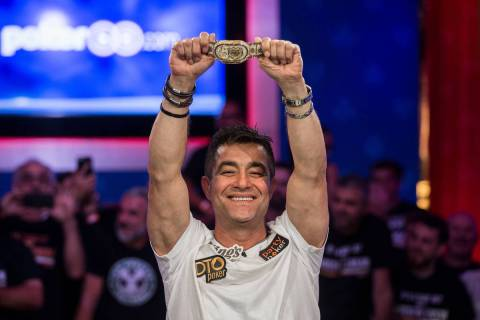 Hossein Ensan, from Germany, lifts the championship bracelet after winning the World Series of ...