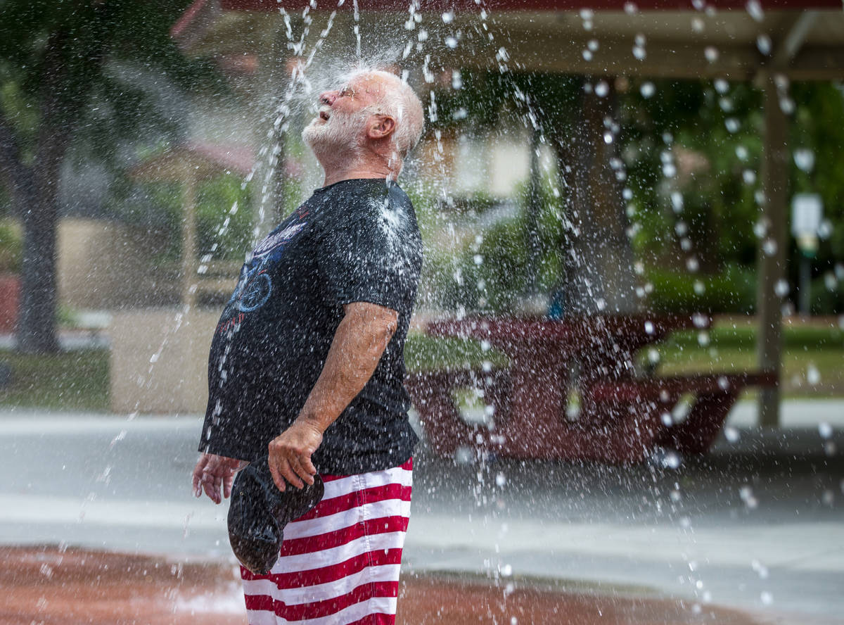 Robert Burnzott cools off in the fountains about the splash pad at Bob Baskin Park on Tuesday, ...