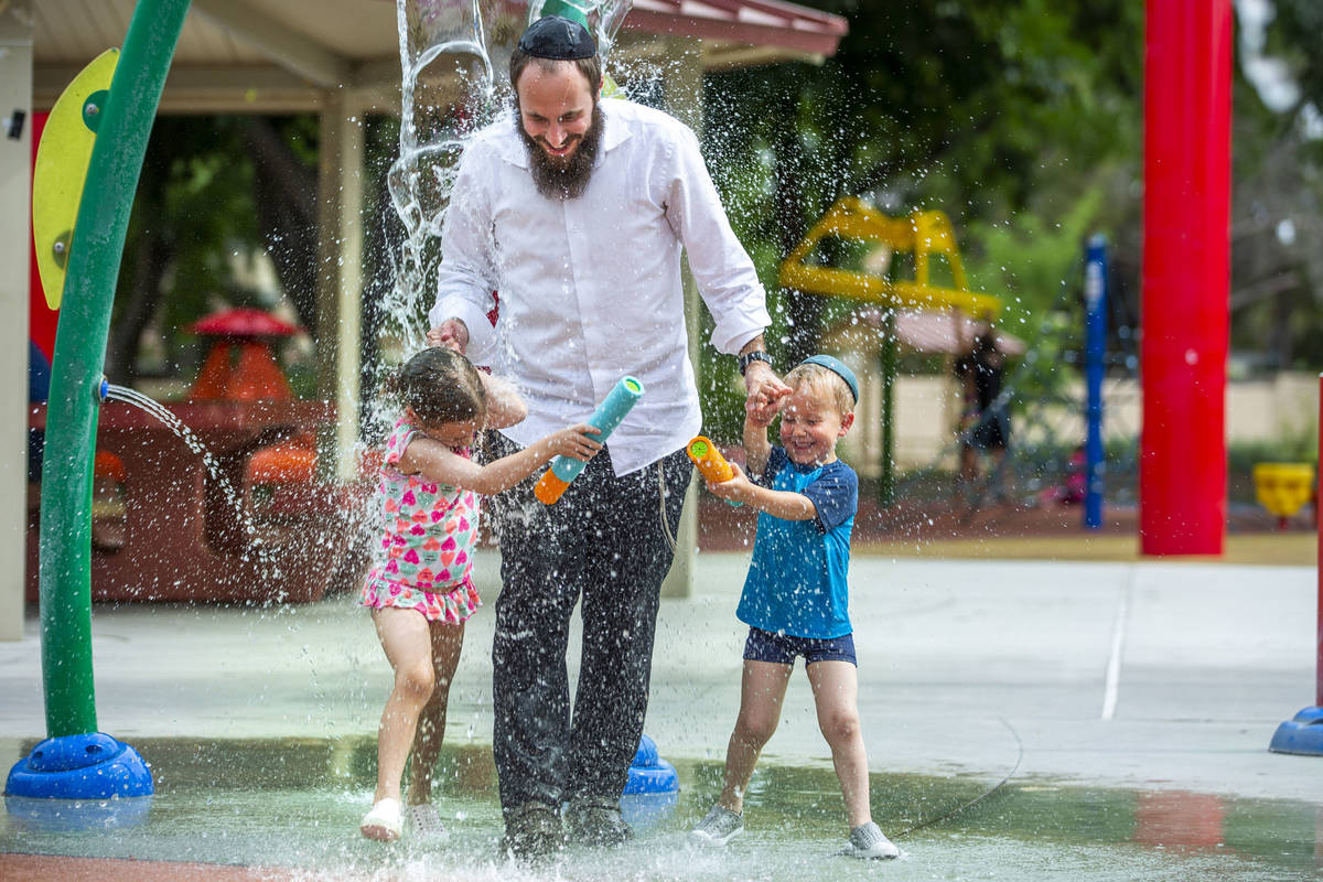 Rabbi Motti Harlig with his children Rivka, 5 , left, and Mendel, 3 right, get doused with wate ...