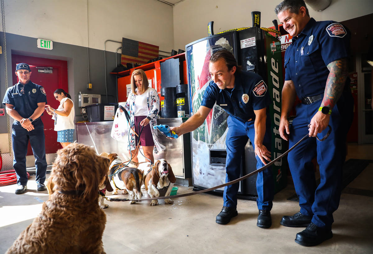 Tyler McFate, Station 1A operations chief, center, hands a toy to Murphy, a golden doodle, next ...