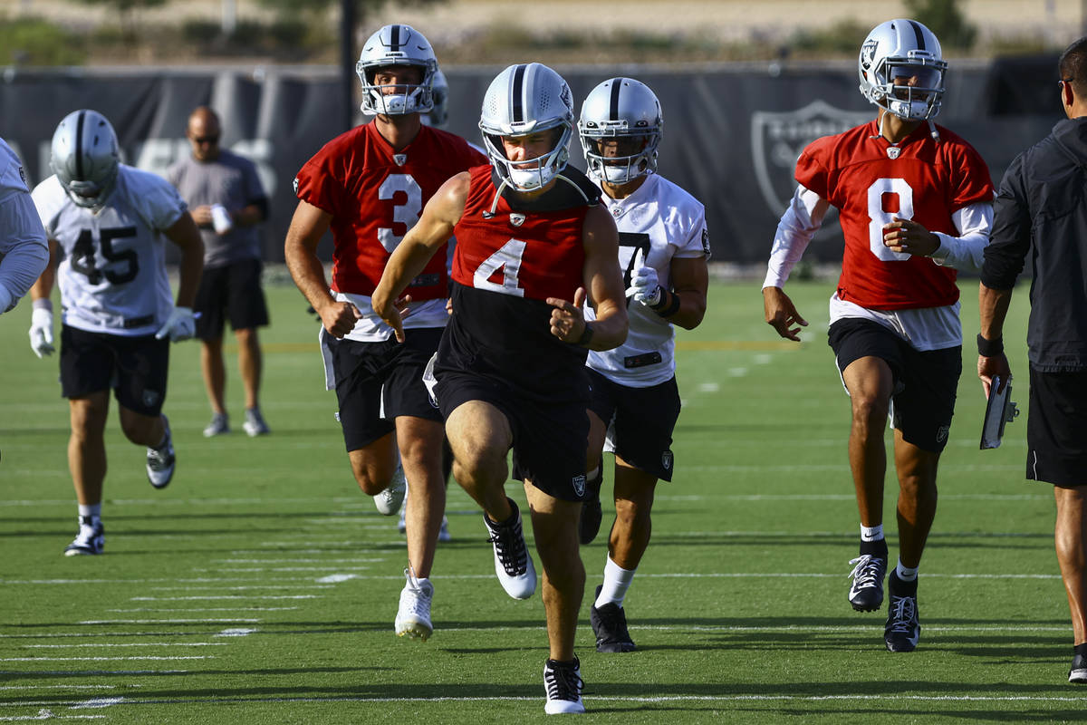 Raiders quarterback Derek Carr (4) warms up with teammates during an NFL football minicamp at R ...