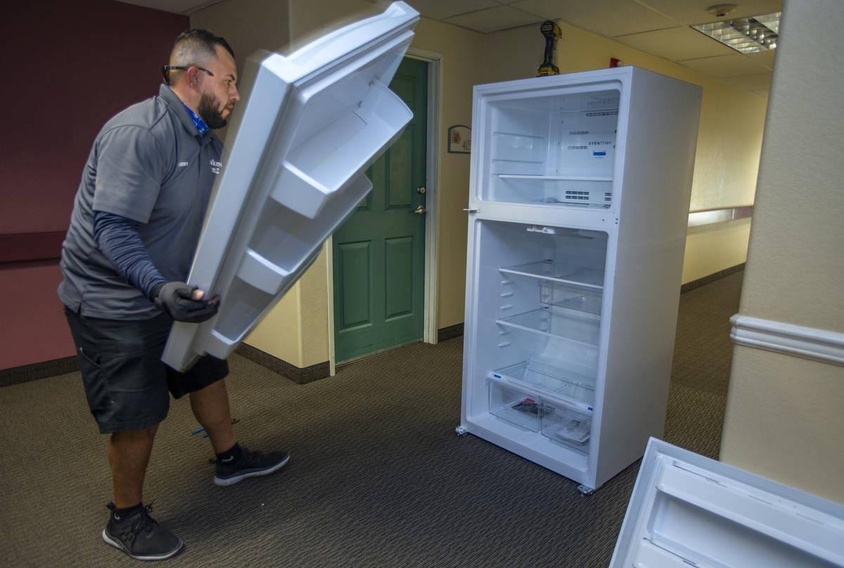 Lowe's employee Albert Vazquez reverses the doors on one of the 98 fridges at Bonanza Pines Sen ...