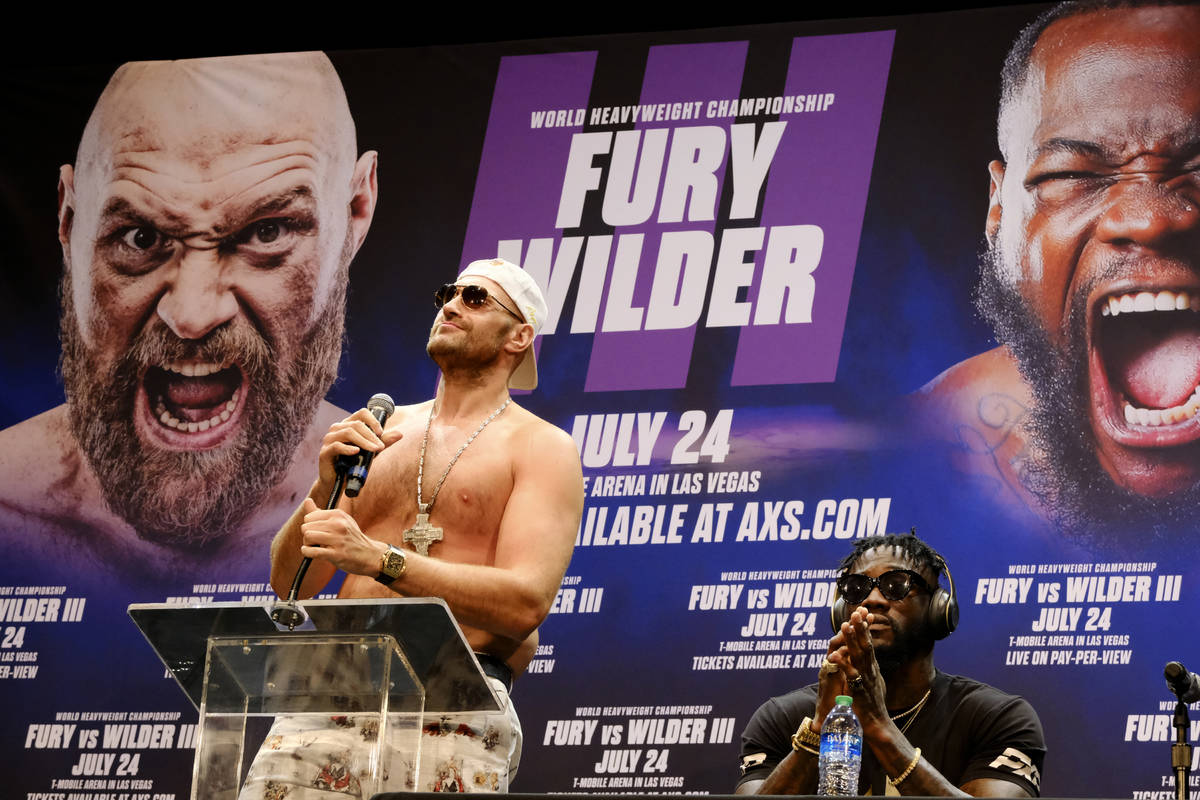 WBC Heavyweight Champion Tyson Fury, left talks during a news conference as Deontay Wilder look ...