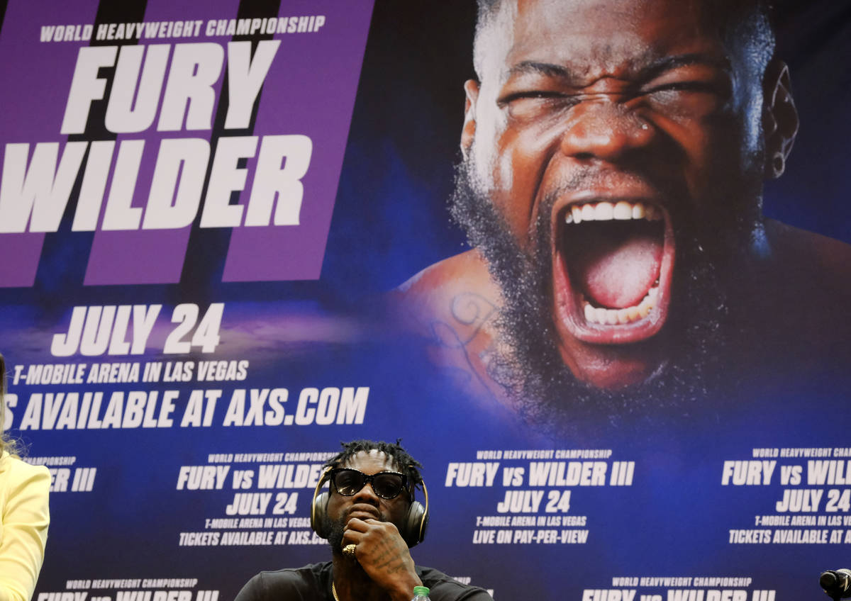 Deontay Wilder wears headphones while sitting during a news conference in Los Angeles on Tuesda ...