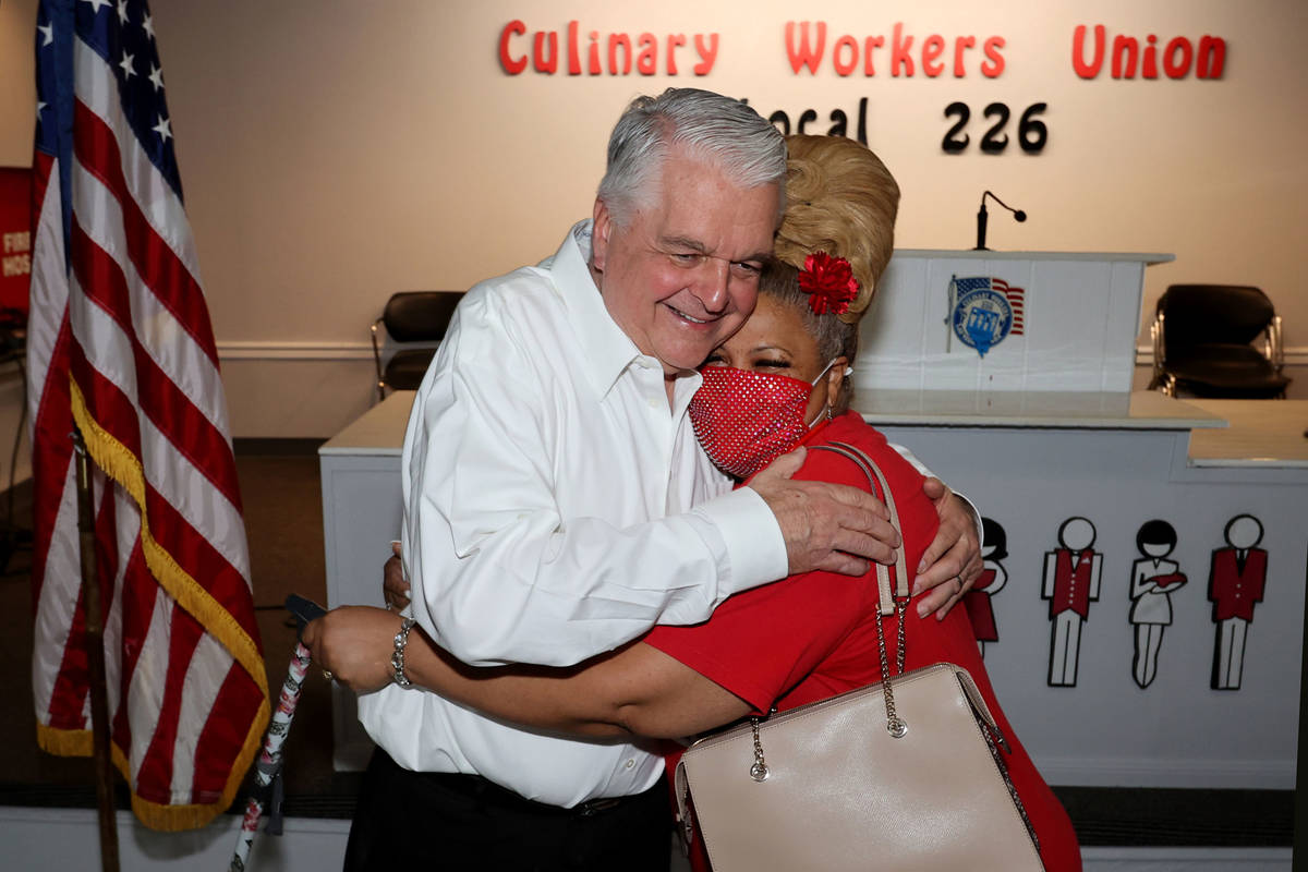 Culinary Workers Union Local 226 member Yolanda Scott, right, greets Gov. Steve Sisolak at her ...