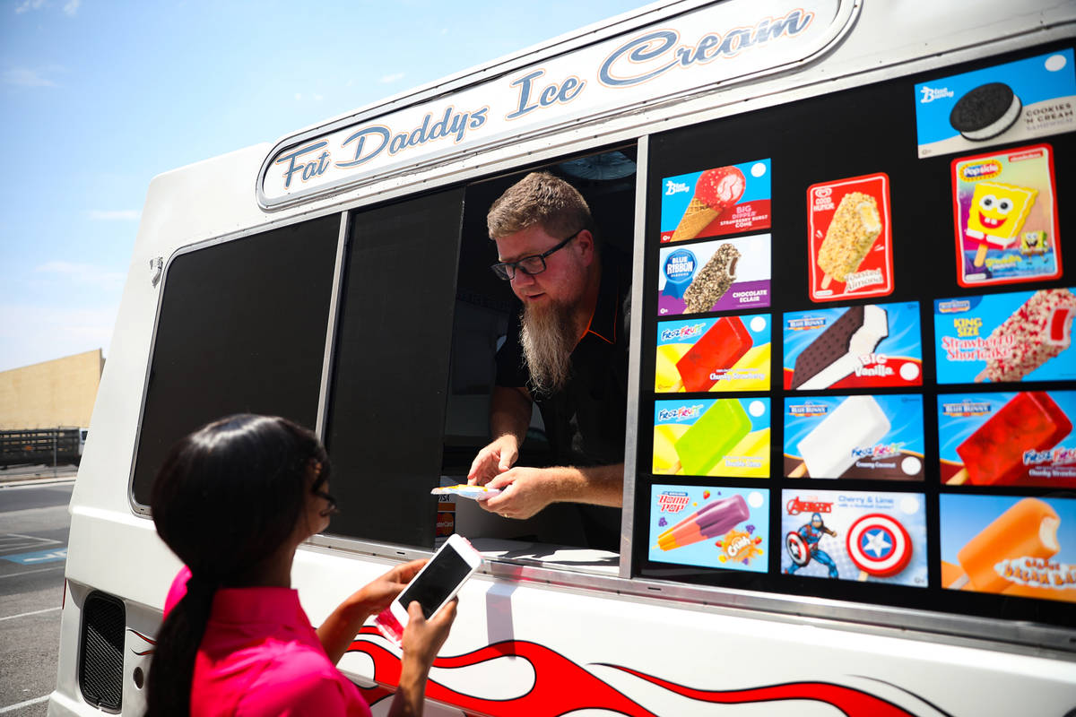 Al Davis, owner of Fat Daddys Ice Cream truck, hands ice cream to Jazmine Eady outside Caliber ...