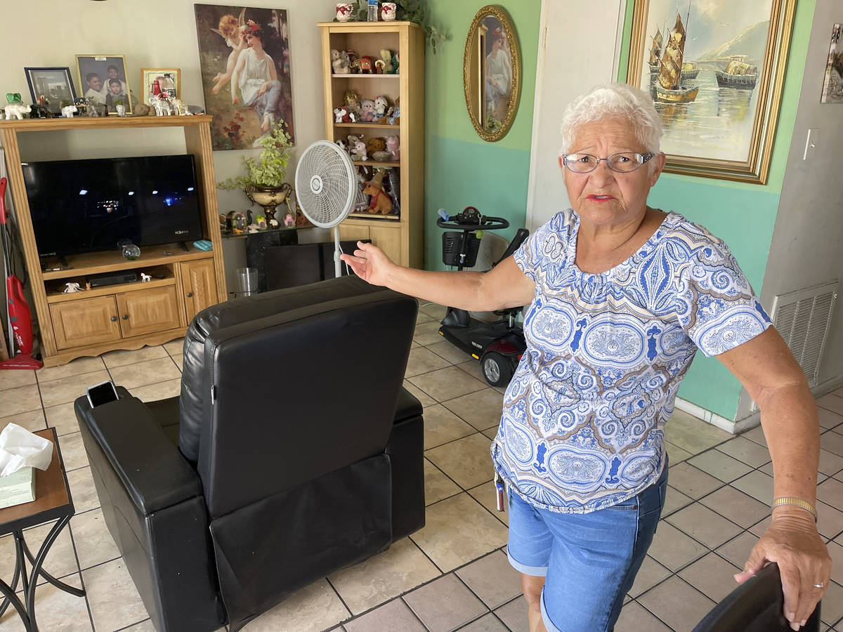 Carmen Millan, 82, shows a fan she uses with open windows and door to keep cool at her apartmen ...