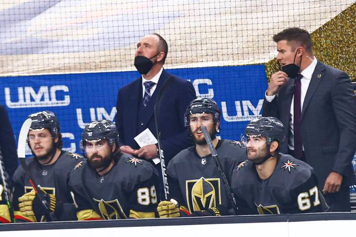 Golden Knights head coach Pete DeBoer, center, looks on from the bench during the first period ...