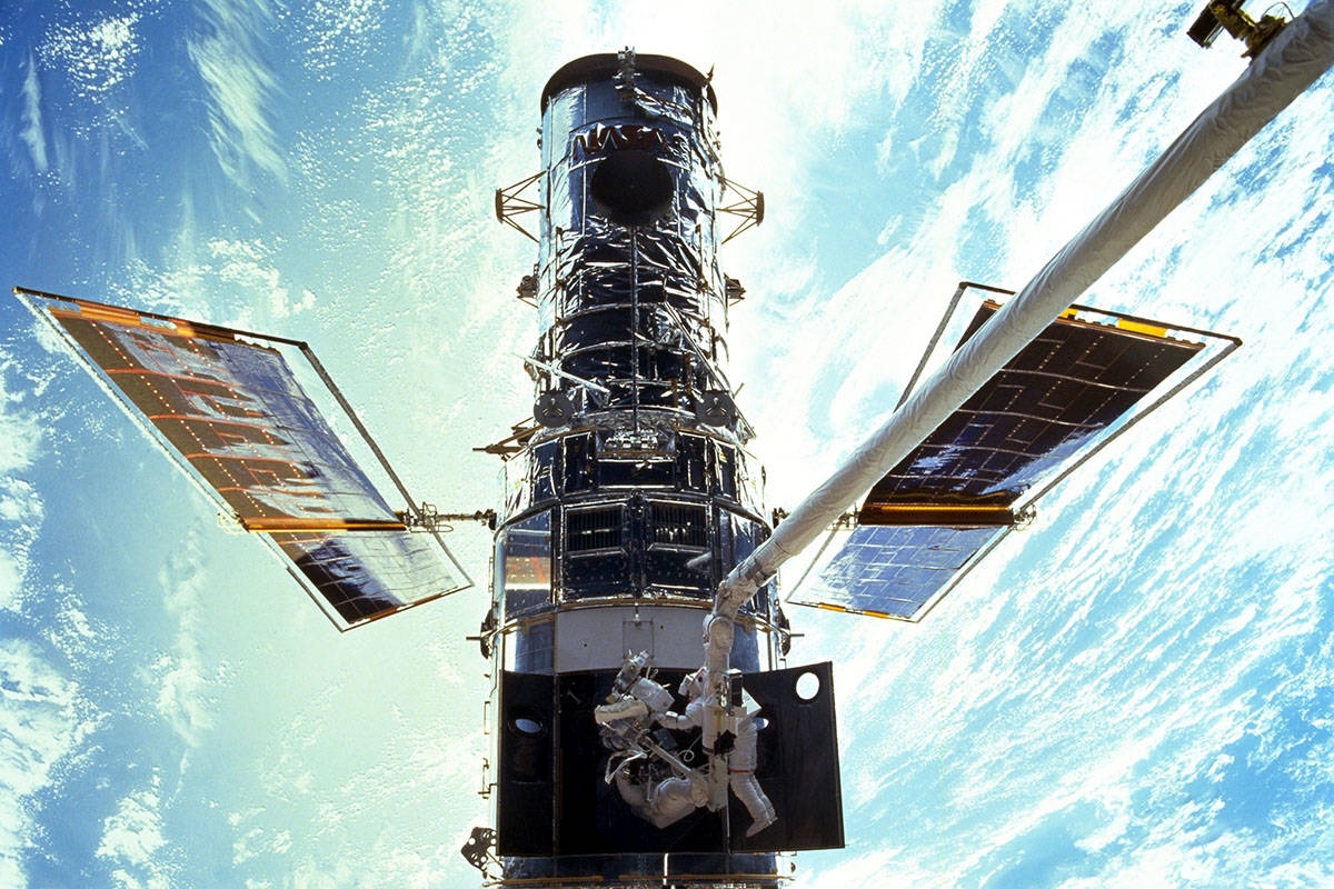 FILE - In this image provided by NASA/JSC, astronauts Steven L. Smith and John M. Grunsfeld are ...