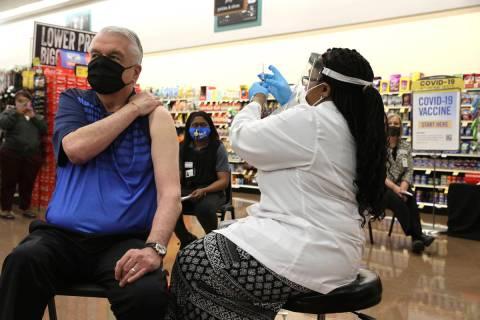 Gov. Steve Sisolak receives his COVID-19 vaccine from Pharmacy Manager Trashelle Miro alongside ...