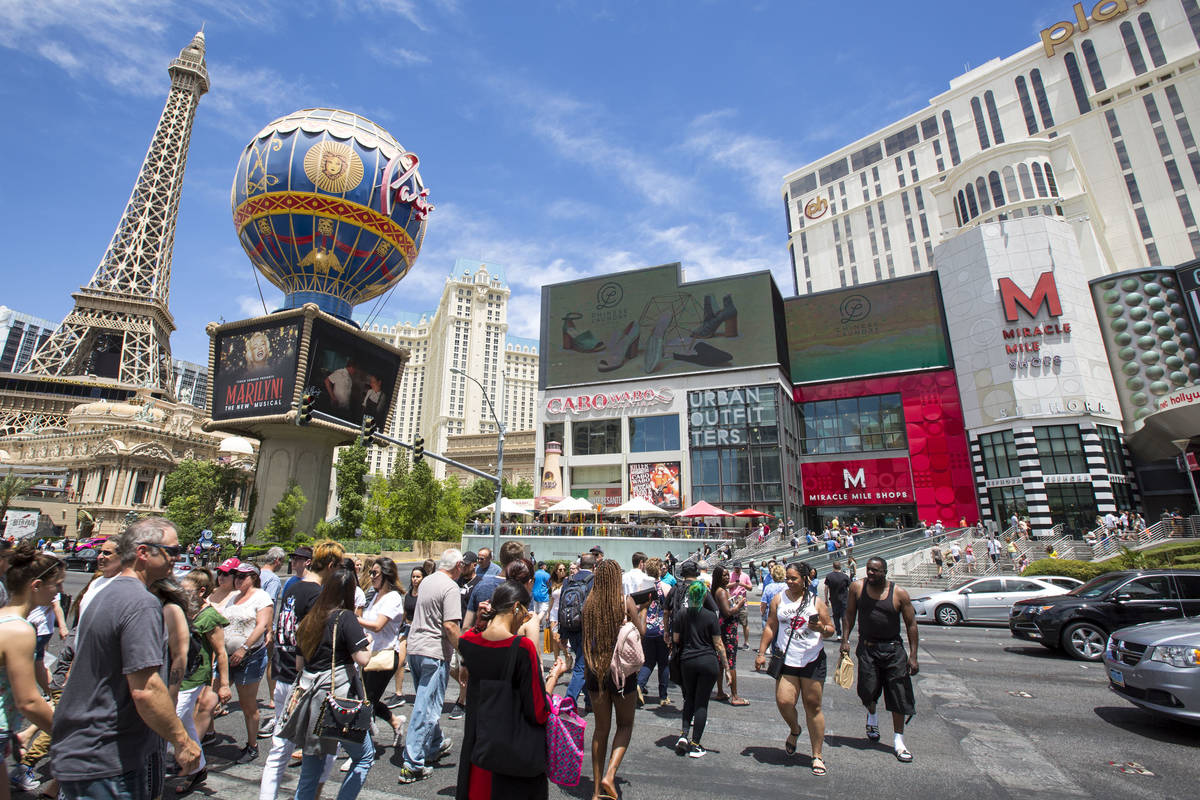 People cross the street outside the Paris Las Vegas and Planet Hollywood Resort on The Strip in ...