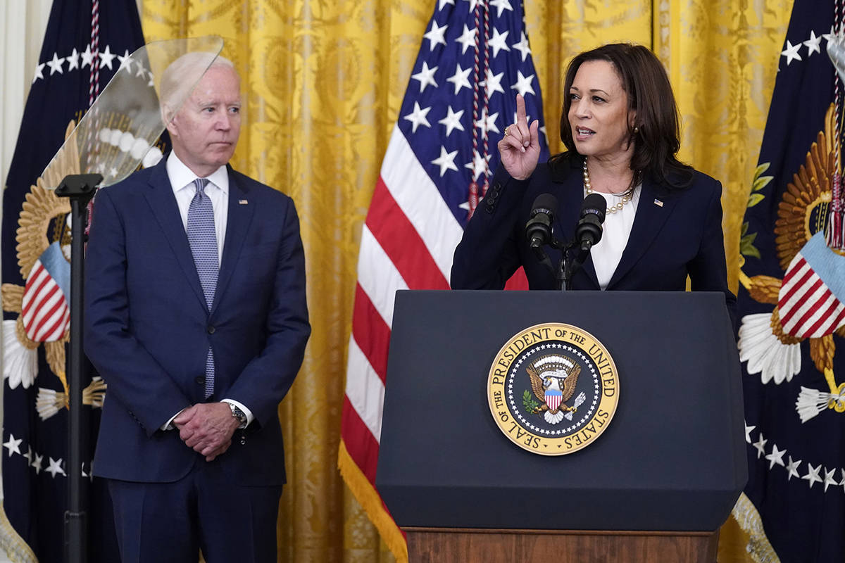 President Joe Biden listens as Vice President Kamala Harris speaks during an event to mark the ...