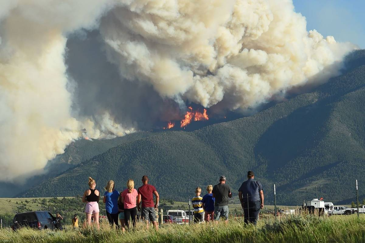 Residents watch as flames from the Robertson Draw fire burn above Red Lodge, Mont., Tuesday eve ...