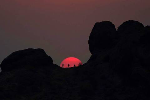Hikers pause to watch the sunset at Papago Park during a heatwave where temperatures reached 11 ...
