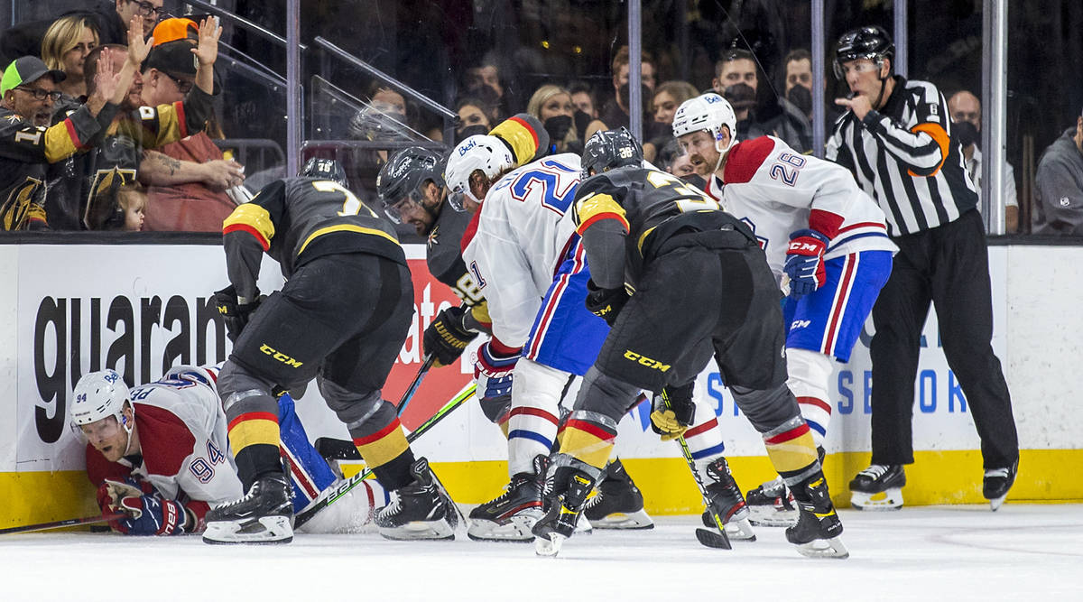 Montreal Canadiens right wing Corey Perry (94) is pummeled on the ice by Golden Knights right w ...