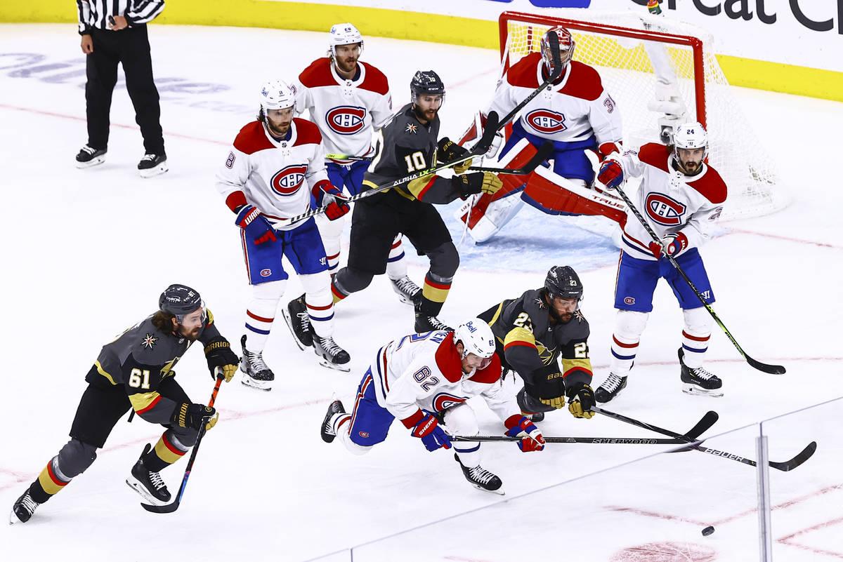 Golden Knights' Alec Martinez (23) and Montreal Canadiens' Artturi Lehkonen (62) vie for the pu ...