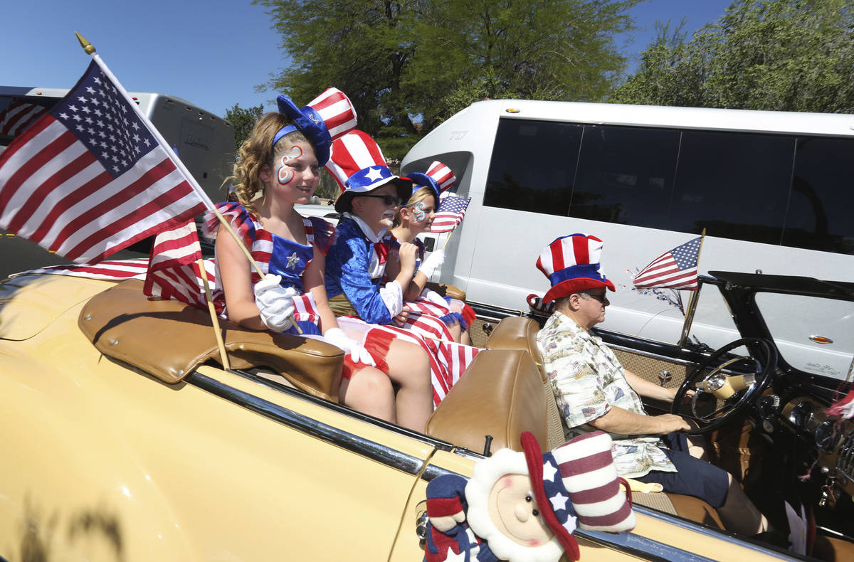 Parade goers wave to spectators in the crowd during the 25th annual Summerlin Council Patriotic ...
