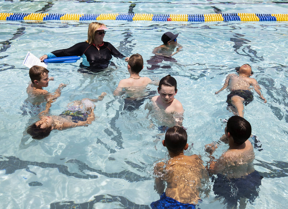 Kim Tyler, a volunteer instructor, watches as children swim during the 12th annual World&#x2019 ...